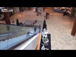 Китайский парень скользит вниз по поручню эскалатора
