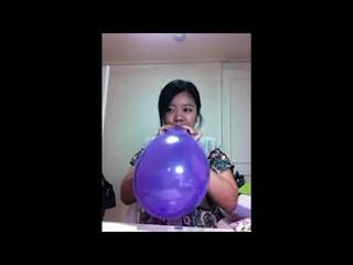 Cute Asian girl blows up a Purple balloon