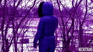 Walking in the winter park of a progressive creature in a dark blue ski overalls and a respirator